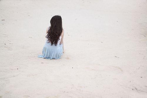 Одинокая девушка на берегу моря